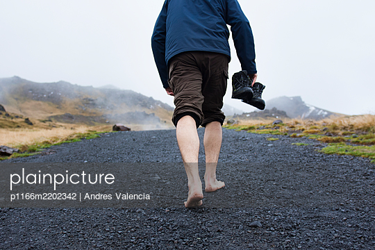 Man walking barefoot along black trail, Reykjadalur, Iceland - p1166m2202342 by Andres Valencia