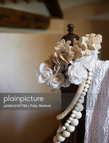 White roses and lace on foot of vintage bed in Sicilian home - p349m2167755 by Polly Wreford