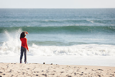 Rear view of boy standing at beach during sunny day - p1166m1474248 by Cavan Images