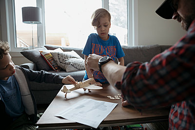 Father and son assembling model airplane, reading instructions in living room - p1192m1567348 by Hero Images