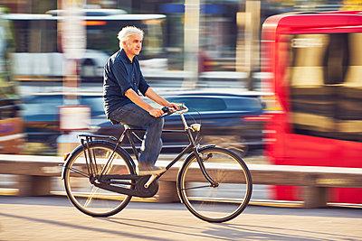 Mann auf dem Fahrrad in der Stadt - p1312m1515408 von Axel Killian