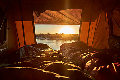 Scenic view of river seen from tent at Caprivi Strip during sunset, Namibia - p300m2144814 by Veam