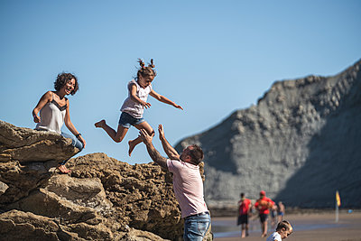 Shocked mother watching daughter jumping onto man at beach - p300m2256617 by SERGIO NIEVAS