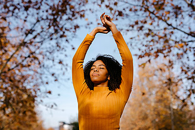 Afro woman with hands raised in park during sunny day - p300m2267489 by Tania Cervián