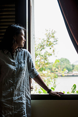 Woman looking out of a window to the Chao Phraya river in Bangkok, Thailand - p429m1156098 by Henn Photography