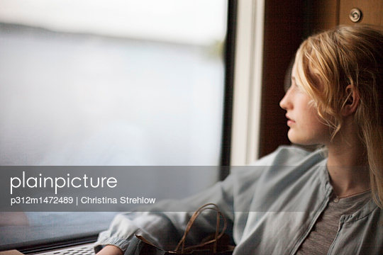 Teenage girl looking through window - p312m1472489 by Christina Strehlow
