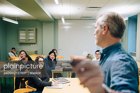Male teacher teaching high school students in classroom - p426m2127691 by Maskot