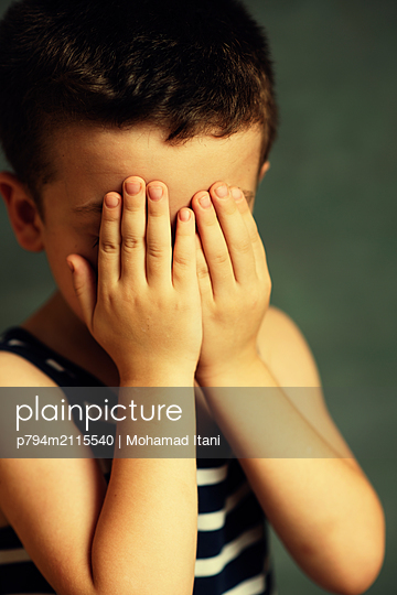 Sad boy hiding face with hands - p794m2115540 by Mohamad Itani