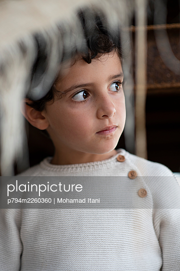Scared little boy looking away  - p794m2260360 by Mohamad Itani