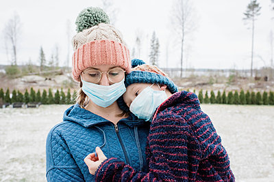mother carrying son with face masks on for protection from virus & flu - p1166m2171950 by Cavan Images