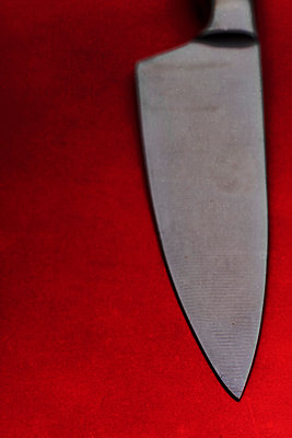 Sharp knife against a red background - p1228m2125851 by Benjamin Harte