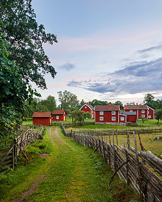 Sweden, Smaland, Stensjo, Rural scene with wooden fence and brown houses - p352m1349341 by Gustaf Emanuelsson