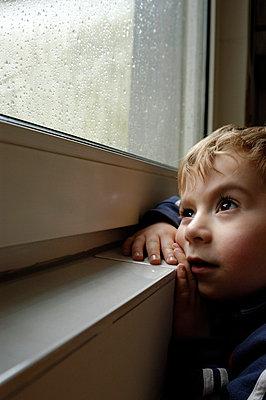 Junge schaut aus verregnetem Fenster - p5200040 von Jasmin Noé
