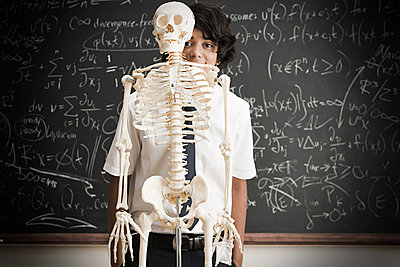 Boy and skeleton in front of blackboard - p9246017f by Image Source