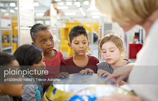 Teacher and curious students at interactive earth exhibit in science center - p1023m2016892 by Trevor Adeline