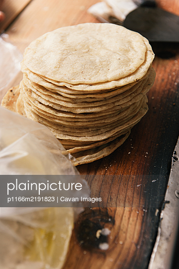 A stack of fresh tortilla shells at a roadside taqueria in Mexico - p1166m2191823 by Cavan Images