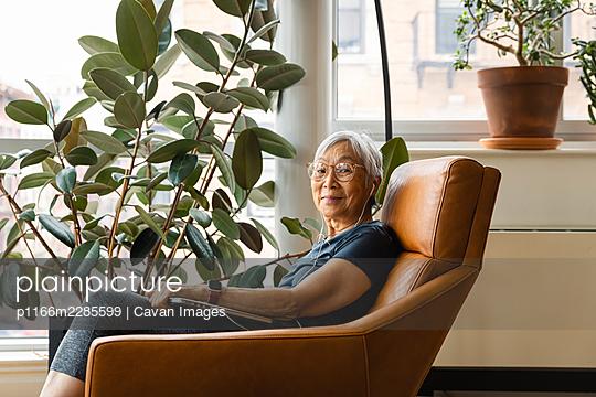 Portrait of senior woman wearing earphones while using laptop at home - p1166m2285599 by Cavan Images