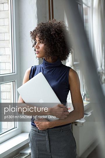 Junge Geschäftsfrau mit Afro hält ihren Laptop und steht am Fenster  - p1301m1582966 von Delia Baum