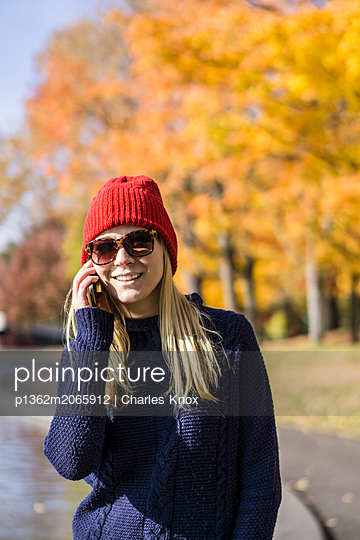 Young blonde woman in park making a phone call, Montreal, Quebec, Canada - p1362m2065912 by Charles Knox