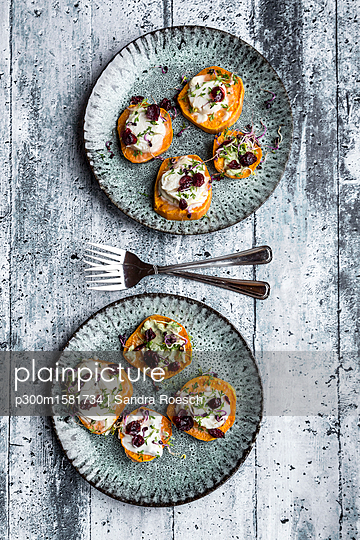 Slices of sweet potato with cream cheese, ramson cream, goat cheese, cress and cranberries - p300m1581734 von Sandra Roesch