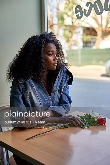 Portrait of young African woman with flowers on the table in a cafe, looking out of window - p300m2140751 by Veam