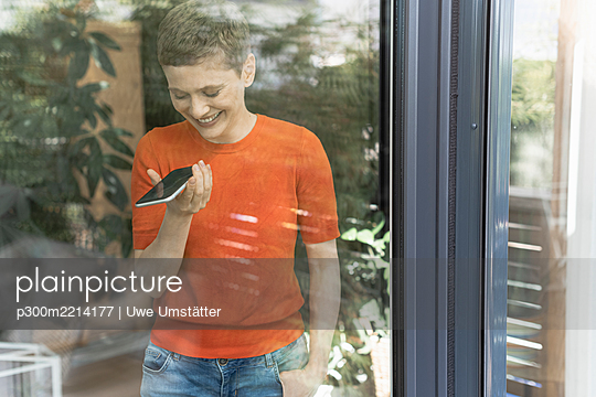 Smiling woman talking over mobile phone while standing by window at home seen through glass - p300m2214177 by Uwe Umstätter