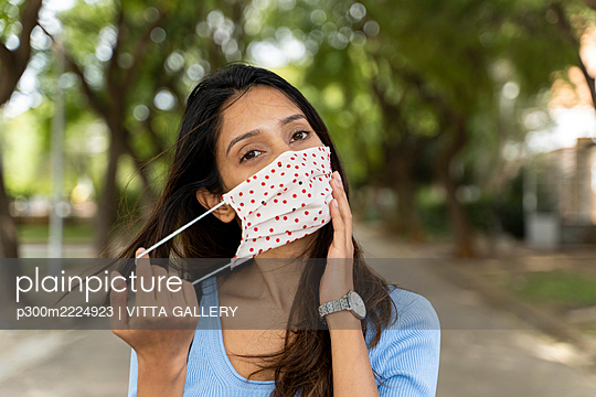 Beautiful woman wearing protective face mask in park during COVID-19 - p300m2224923 by VITTA GALLERY