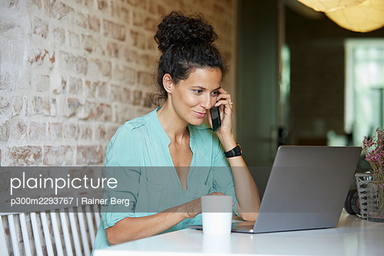 Female professional talking on mobile phone while using laptop at workplace - p300m2293767 by Rainer Berg