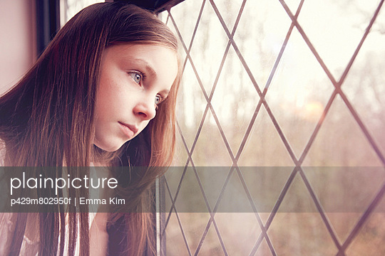 Young girl looking though window - p429m802950f by Emma Kim