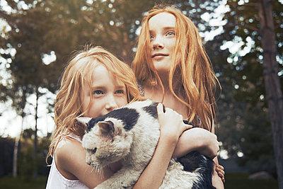 Sisters holding cat - p1023m2088069 by Arman Zhenikeyev