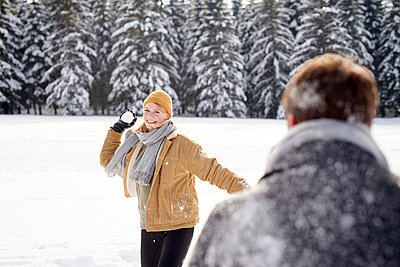 Young couple having a snowball fight - p1124m1589320 by Willing-Holtz