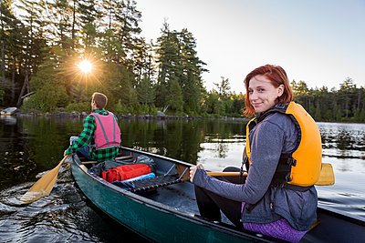 A Young Couple Paddles A Canoe On Long Pond In Maine's North Woods Near Greenville, Maine - p1424m1500714 by Jerry Monkman