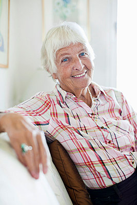 Portrait of smiling senior woman sitting on sofa - p4269315f by Maskot