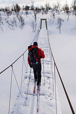Skier on a footbridge Sweden - p5751666f by Fredrik Schlyter