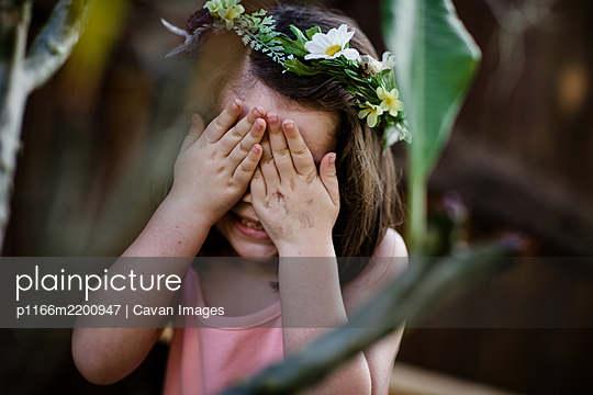 Young girl with flower crown covering eyes - p1166m2200947 by Cavan Images