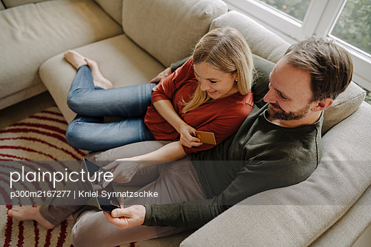 Couple sitting at home on couch, using digital tablet - p300m2167277 by Kniel Synnatzschke
