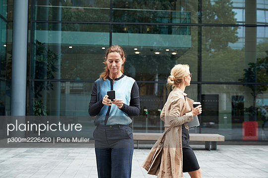 Businesswoman using mobile phone with colleague leaving after work in background - p300m2226420 by Pete Muller