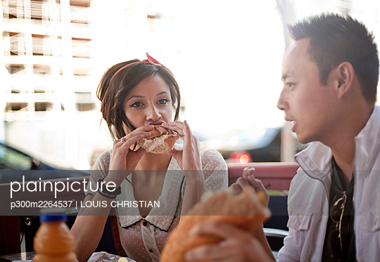 Beautiful woman and handsome man eating sandwich at sidewalk cafe - p300m2264537 by LOUIS CHRISTIAN