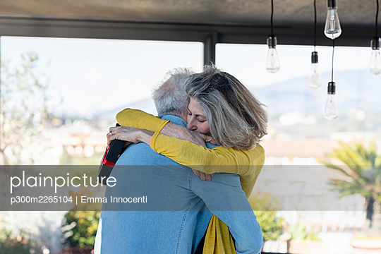 Woman with gift box embracing man at home - p300m2265104 by Emma Innocenti