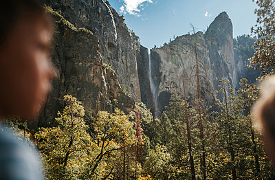 Low angle scenic view of waterfall with boy in foreground at Yosemite National Park - p1166m1526856 by Cavan Images