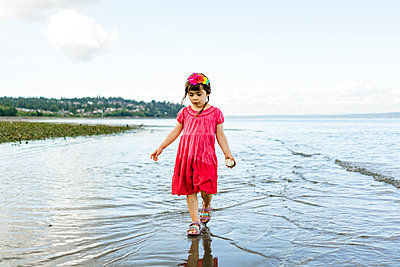 Straight on view of a young girl wading through shallow water - p1166m2289954 by Cavan Images