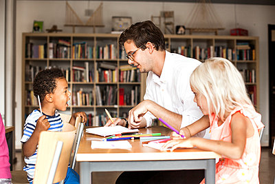 Male teacher teaching students during art class - p1185m994175f by Astrakan