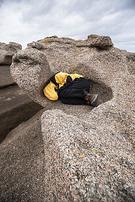 Man curled up in the hollow of a rock carved by the sea - p1682m2263438 by Régine Heintz