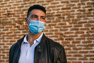 Young man wearing face mask standing against brick wall - p300m2224855 by Andrés Benitez