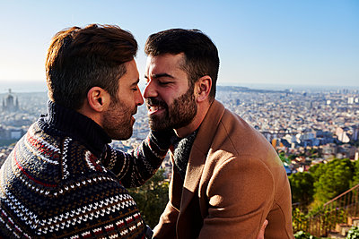 Gay men romancing while sitting against cityscape, Bunkers del Carmel, Barcelona, Spain - p300m2256695 by Veam