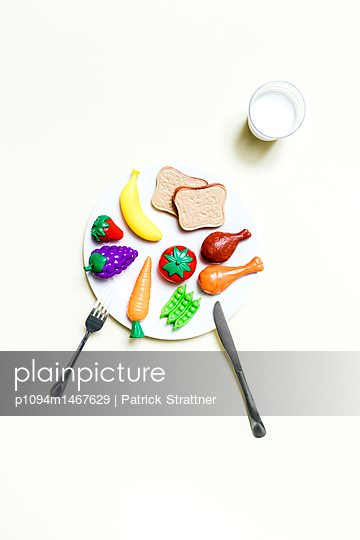 Directly above view of healthy food pyramid plate on yellow background - p1094m1467629 by Patrick Strattner