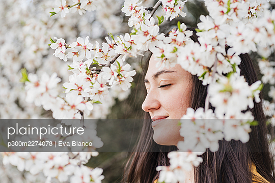 Smiling beautiful woman with eyes closed seen through flowers during springtime - p300m2274078 by Eva Blanco