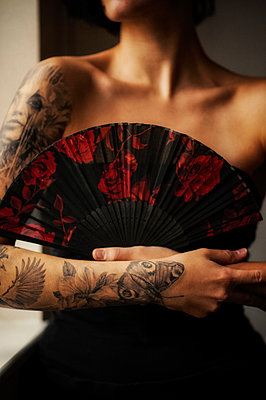 Woman with tattoos holding a fan - p1047m1510662 by Sally Mundy