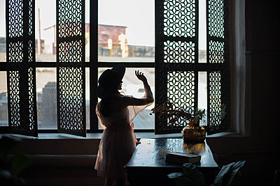 Silhouette of a woman with hat by the window - p1642m2216214 by V-fokuse