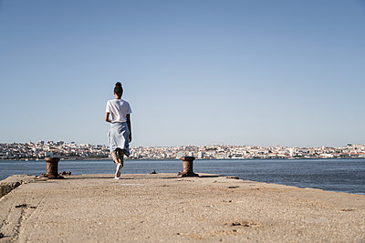 Young woman walking on pier at the waterfront, Lisbon, Portugal - p300m2144512 by Uwe Umstätter